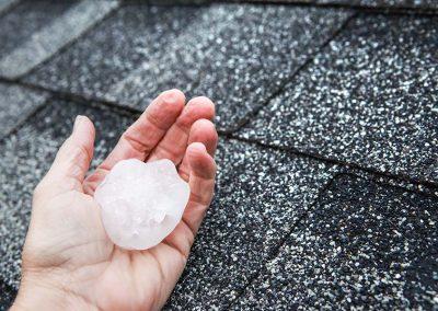 Large Hailstone Near Asphalt Roof